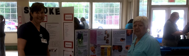 Picture of a public health nurse standing next to a booth at a community event