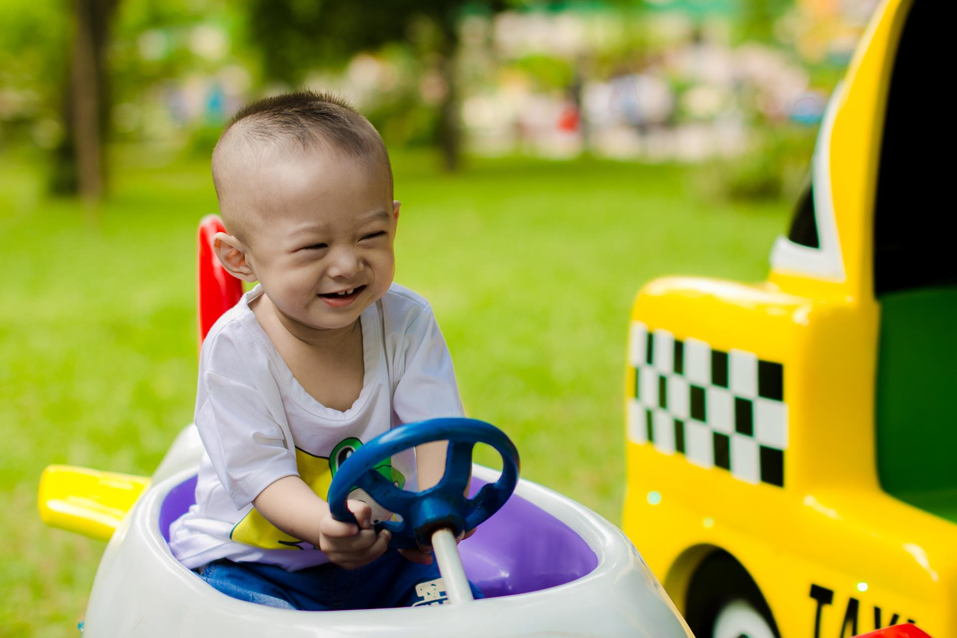 Canva - Boy Smiling While Riding Ride-on Toy